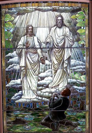 A stain glass window showing Joseph Smith, God, and Jesus Christ during the First Vision.